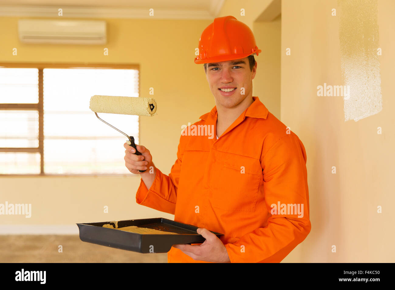 young contractor painting inside the house - Stock Image