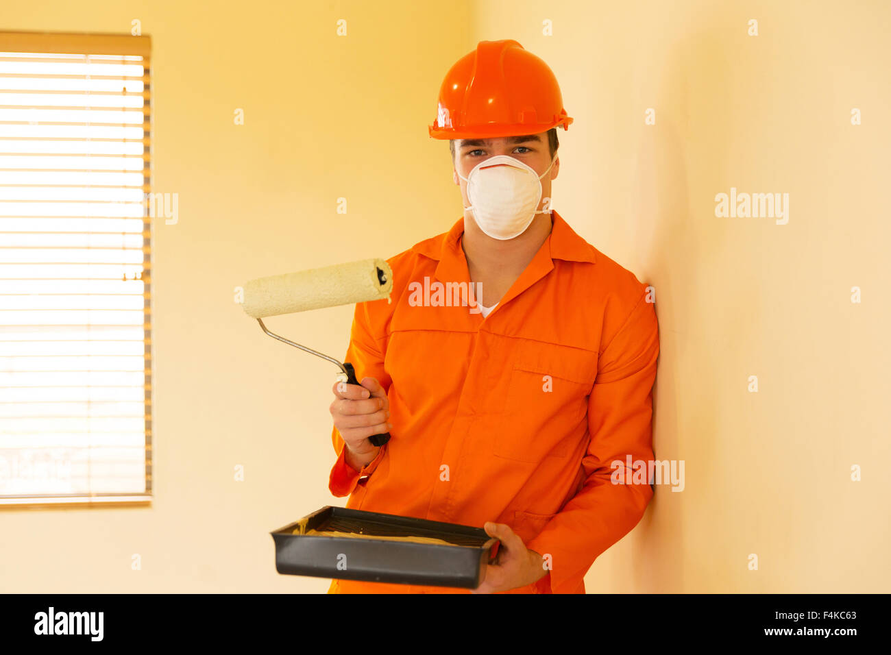 professional painter at work inside a house - Stock Image