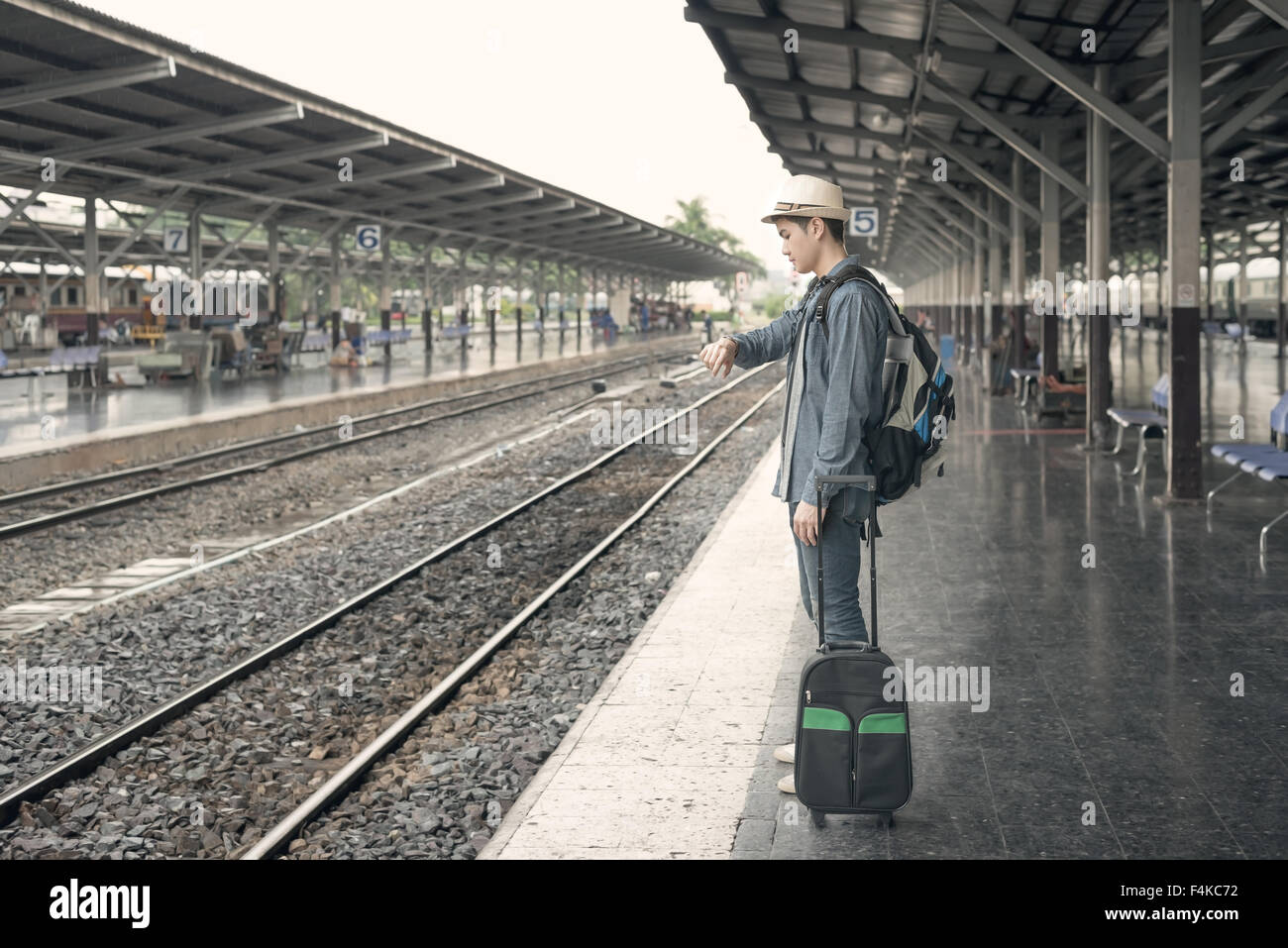 Train delay. Young asian man looking in his watch while waiting train at station - Stock Image