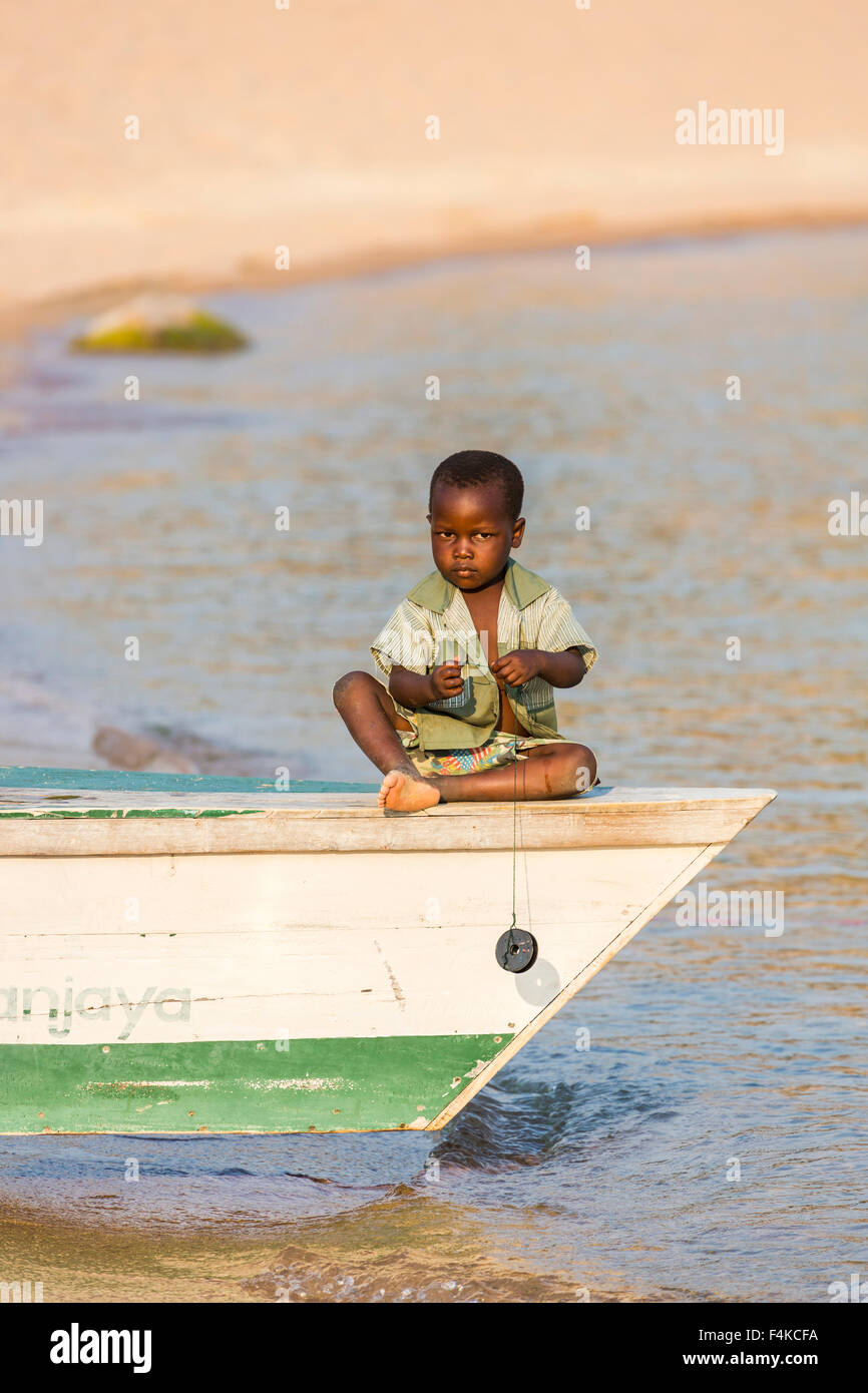 Local African boy playing at fishing from a fishing boat, Kaya Mawa, Likoma Island, Lake Malawi, Malawi, south-east - Stock Image