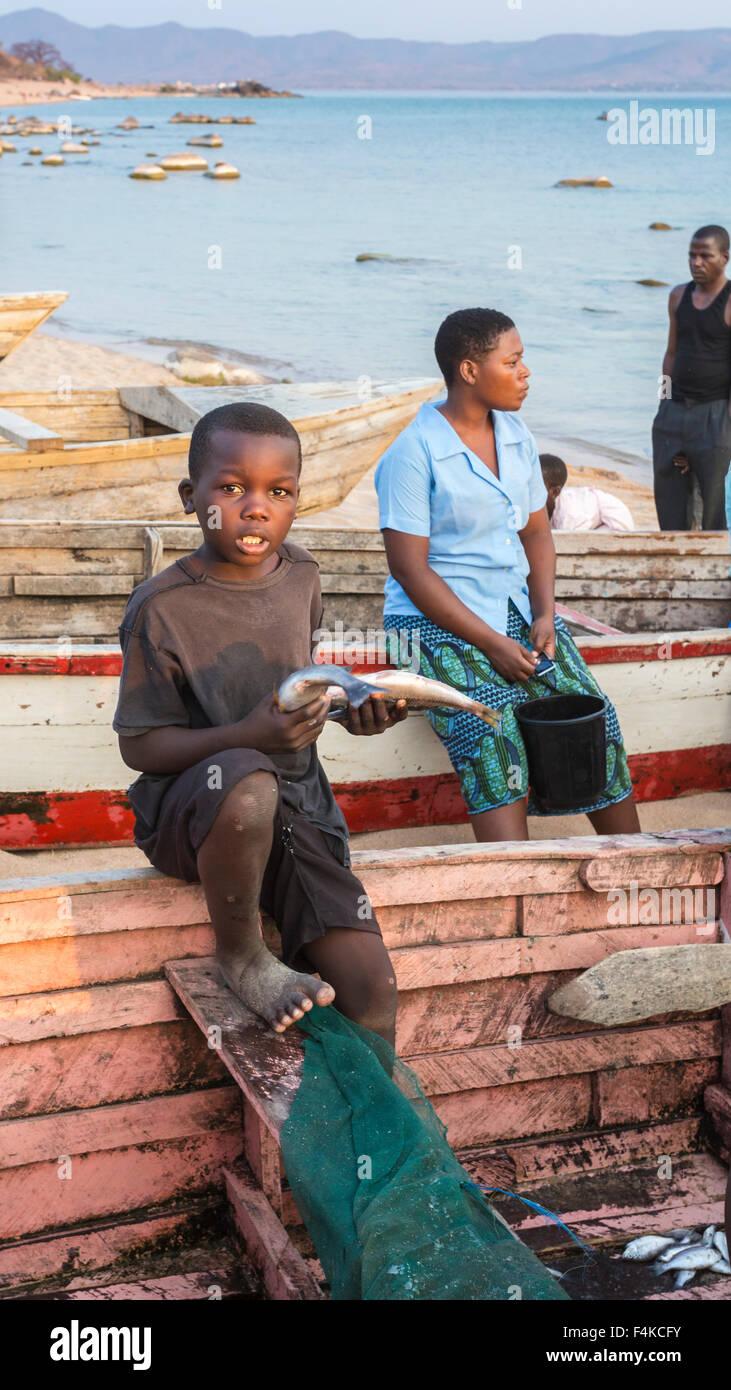 Local boy with fish from the returning fishermen's catch, Likoma Island, Lake Malawi, Malawi, south-east Africa Stock Photo
