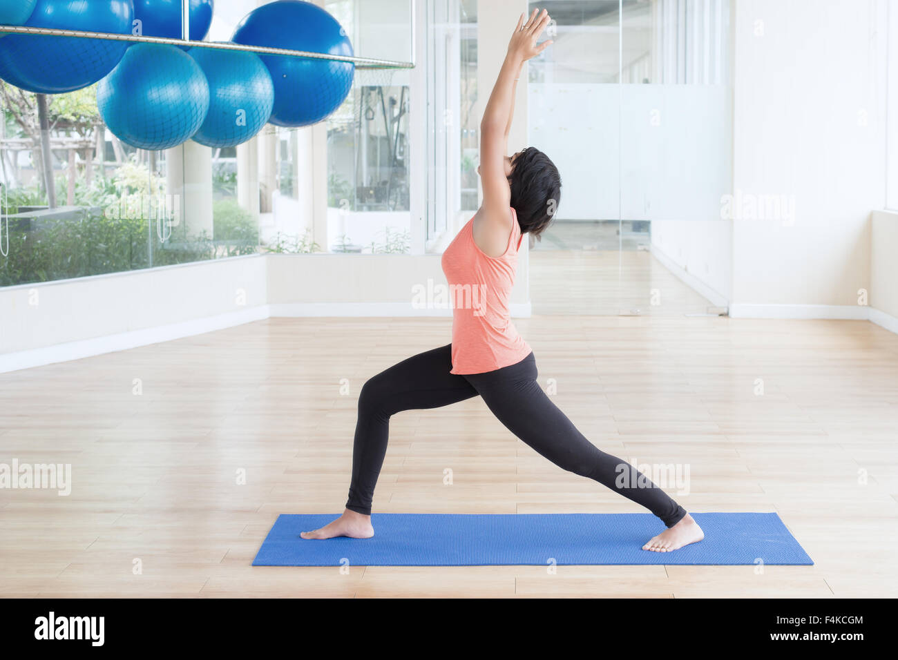 Asian woman make yoga Warrior pose, right leg forward, left leg straight in classroom - Stock Image