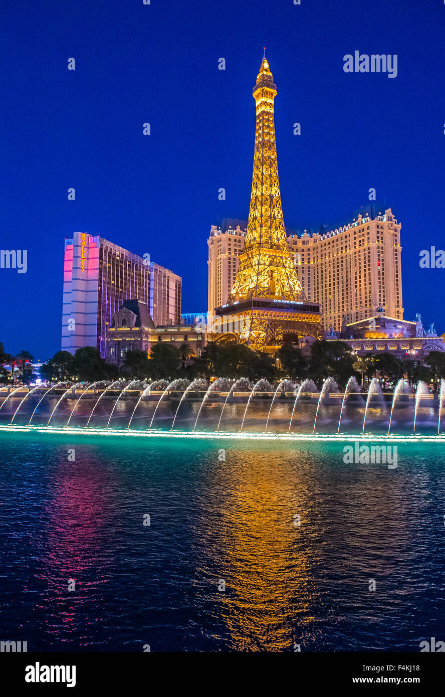 Night view of the dancing fountains of Bellagio and the Eiffel Tower replica of Paris hotel in Las Vegas - Stock Image