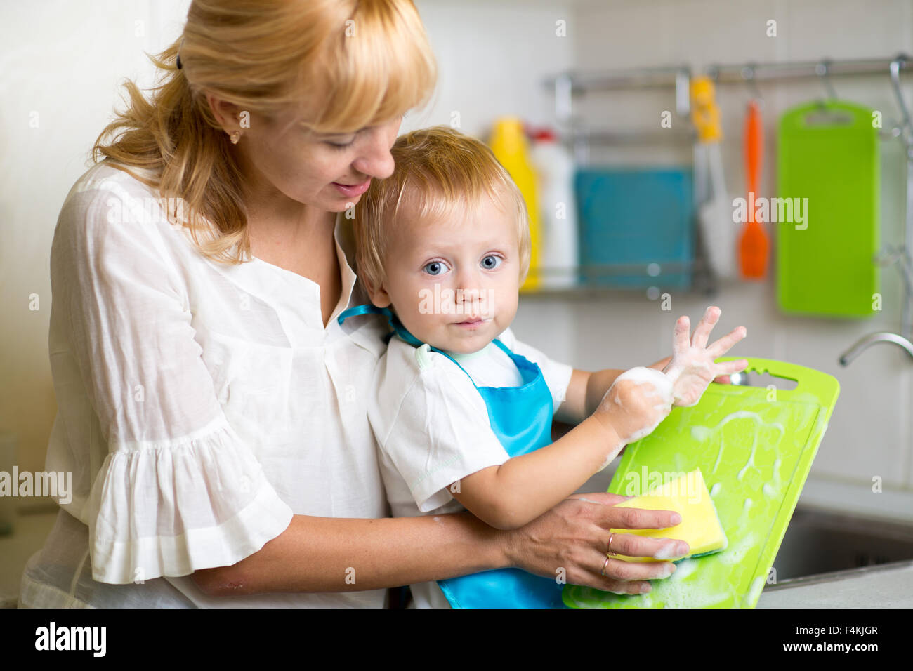 Mother And Kid Son Washing Dishes - Stock Image