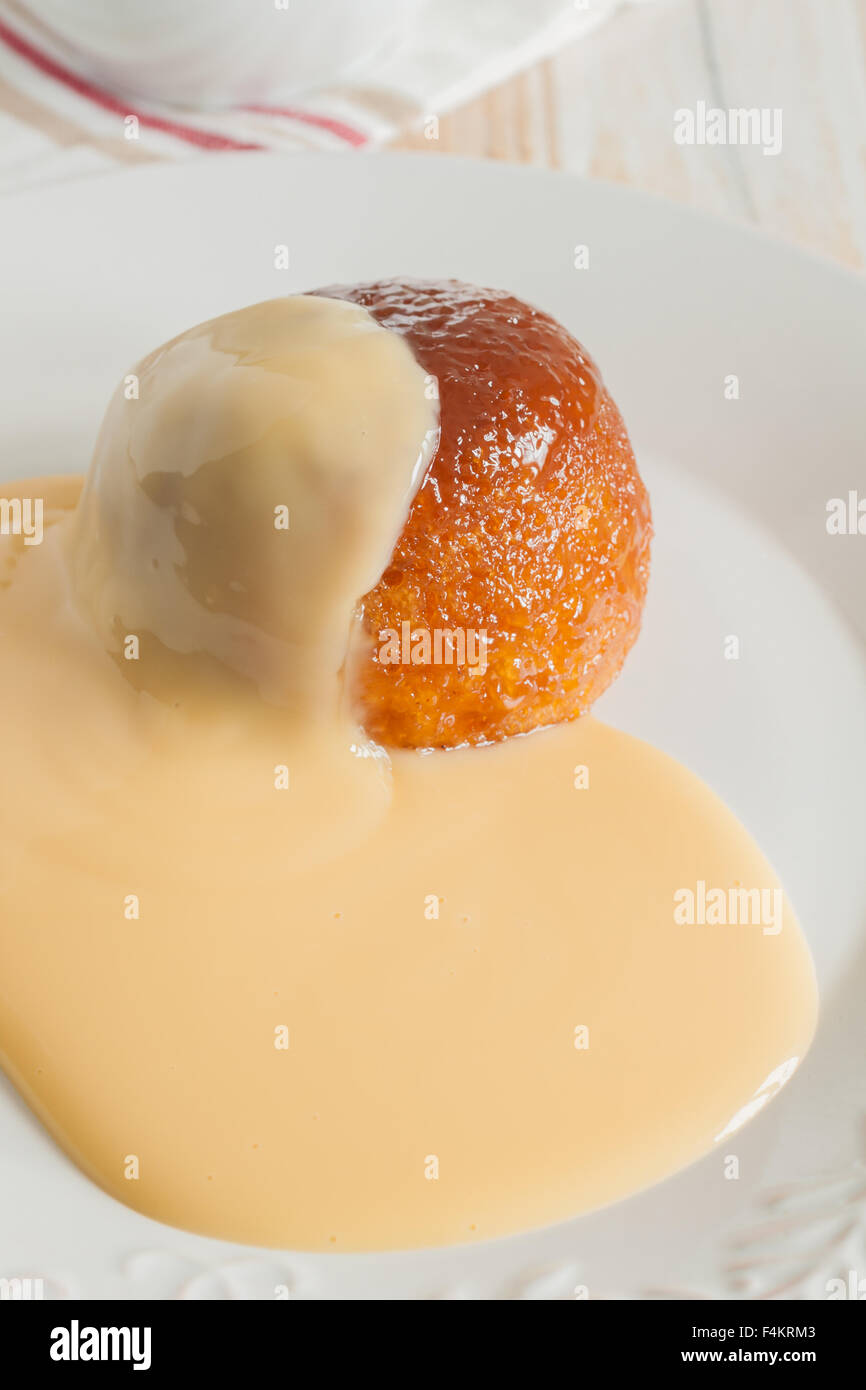 Steamed golden syrup sponge pudding and vanilla custard - Stock Image