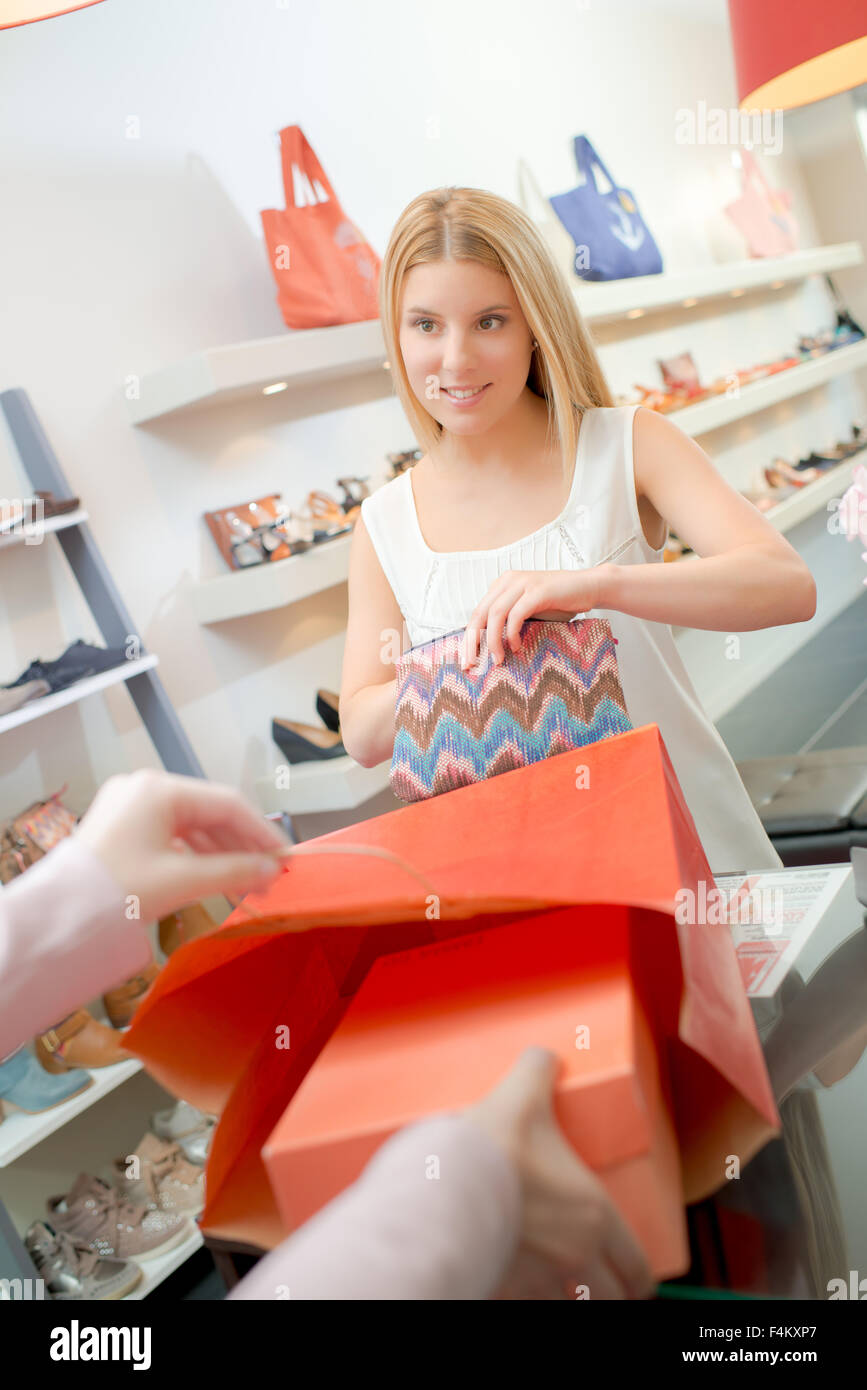 Lady at checkout buying shoes - Stock Image
