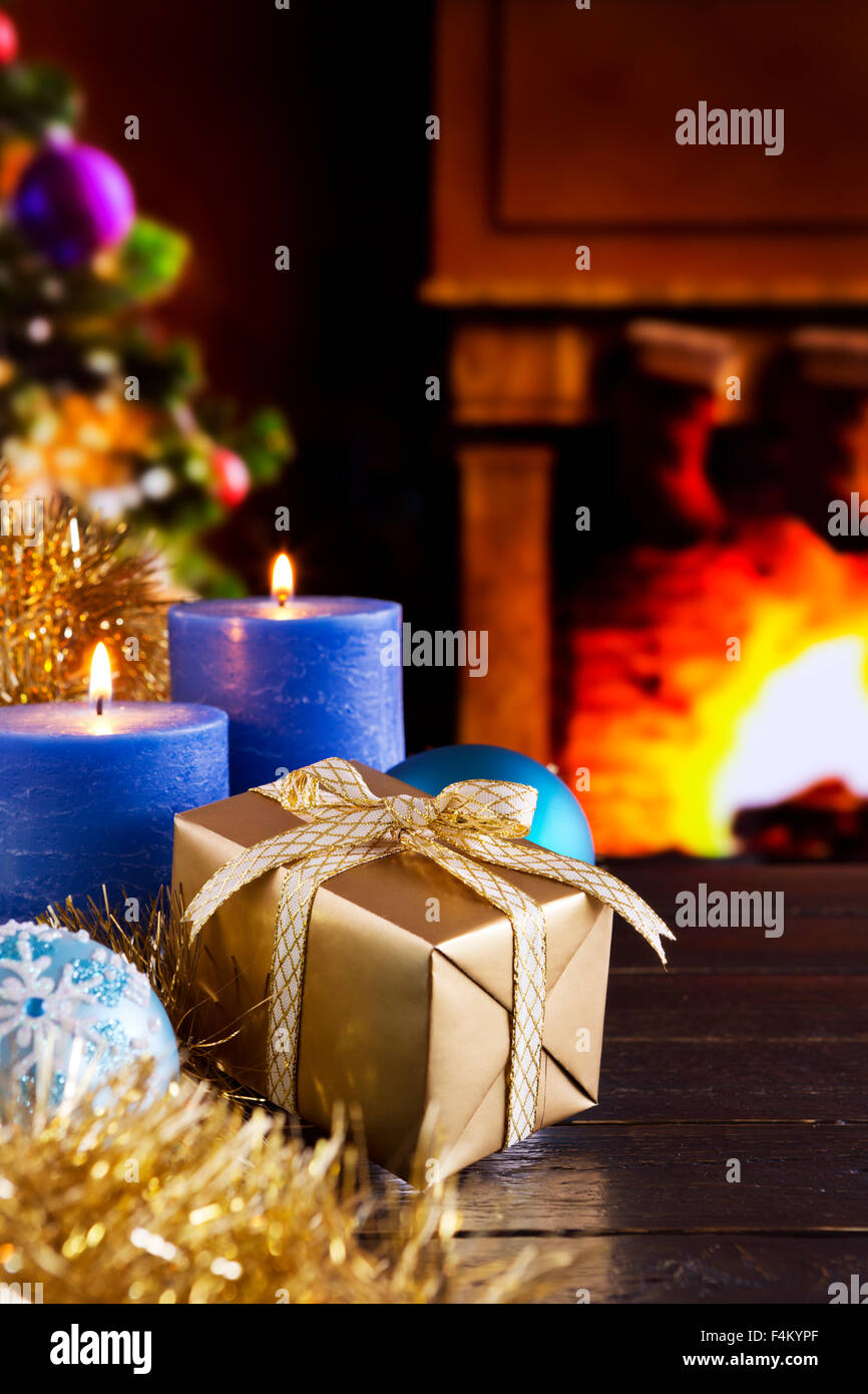 Christmas decorations, a gift and candles in front of a fireplace. A fire is burning in the fireplace and Christmas Stock Photo
