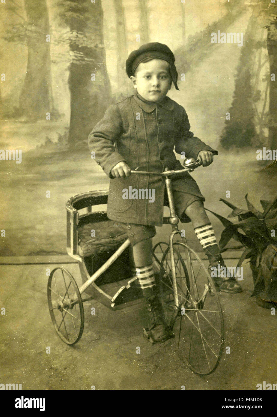 Child on tricycle, Italy - Stock Image