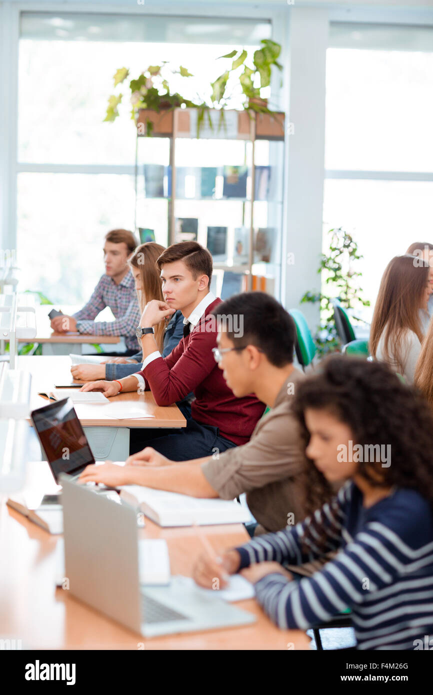 Portrait of a multi ethnic students studying in university library - Stock Image