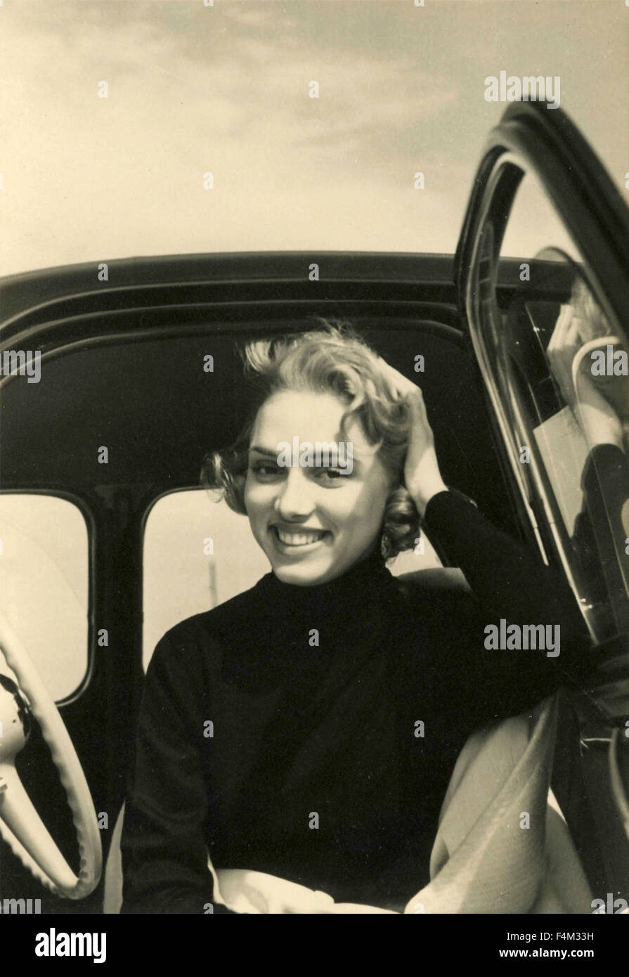 Girl smiles from inside a car, Italy - Stock Image