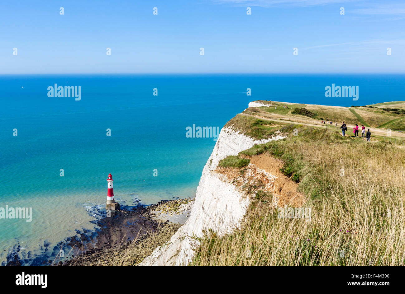 Walkers on the clifftop path overlooking the lighthouse at Beachy Head, near Eastbourne, East Sussex, England, UK - Stock Image