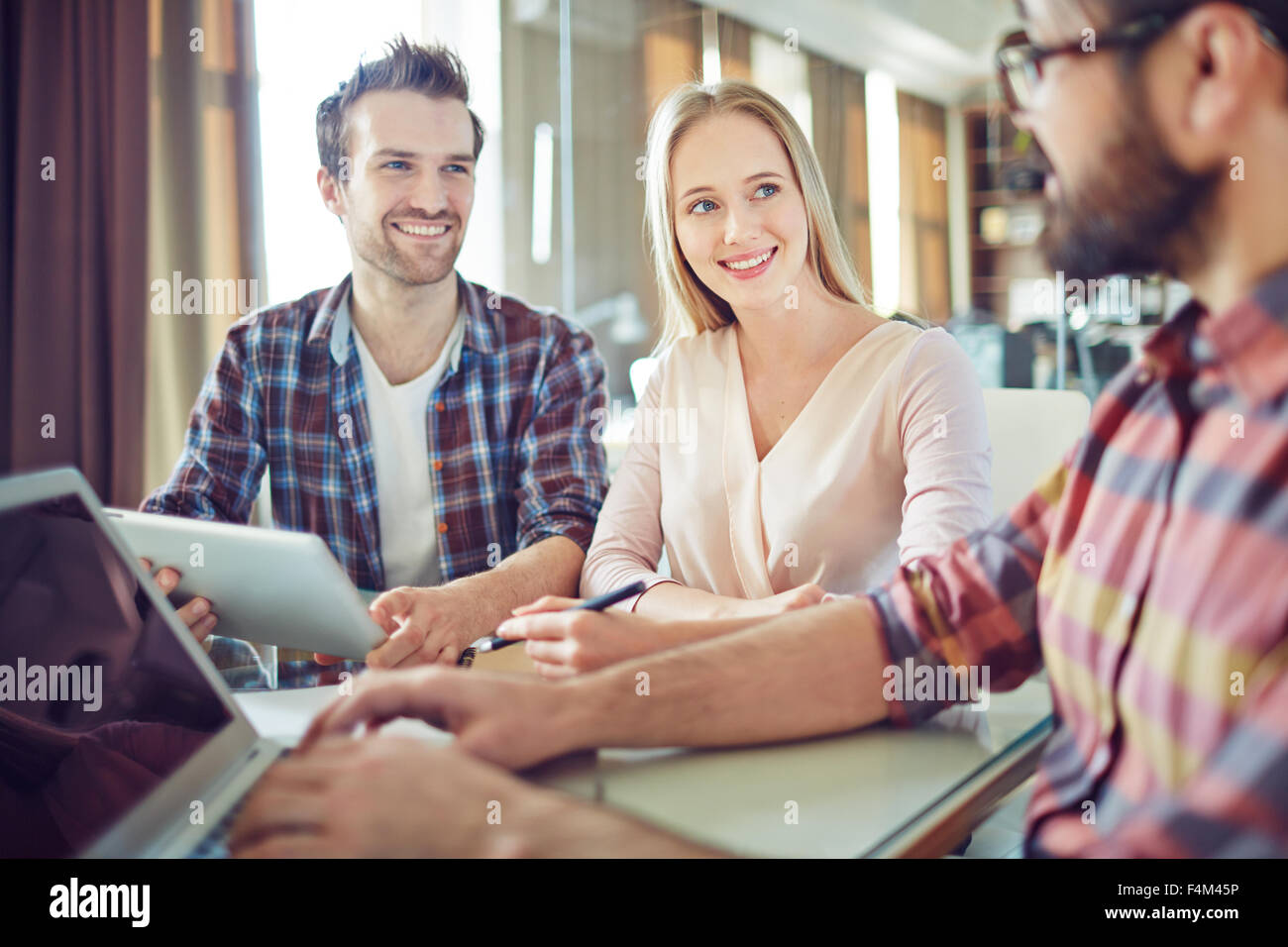 Confident colleagues looking at their co-worker during consultation - Stock Image