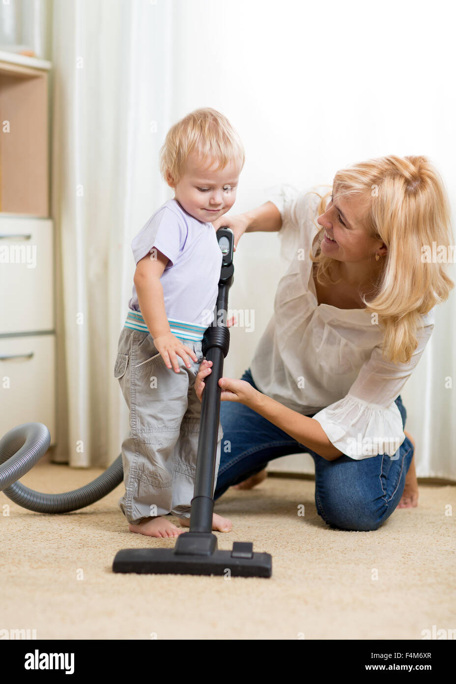 family have fun with cleaning with hoover - housework - Stock Image