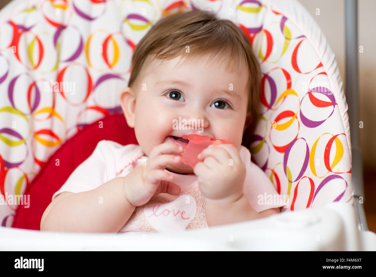 Baby with teething ring sitting in craddle Stock Photo