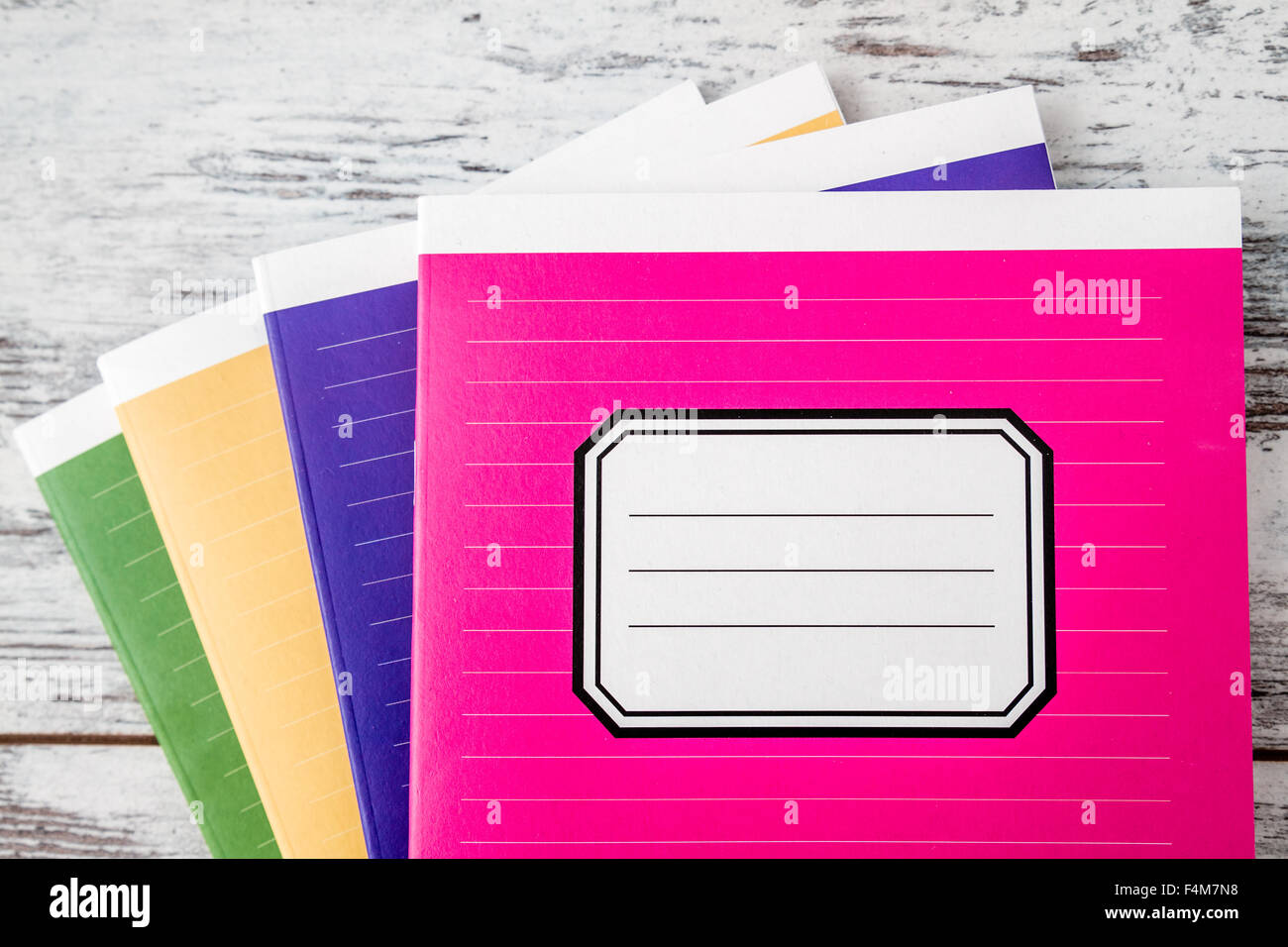 082234c34316 Colorful notebooks with name label on cover on white wooden background -  Stock Image