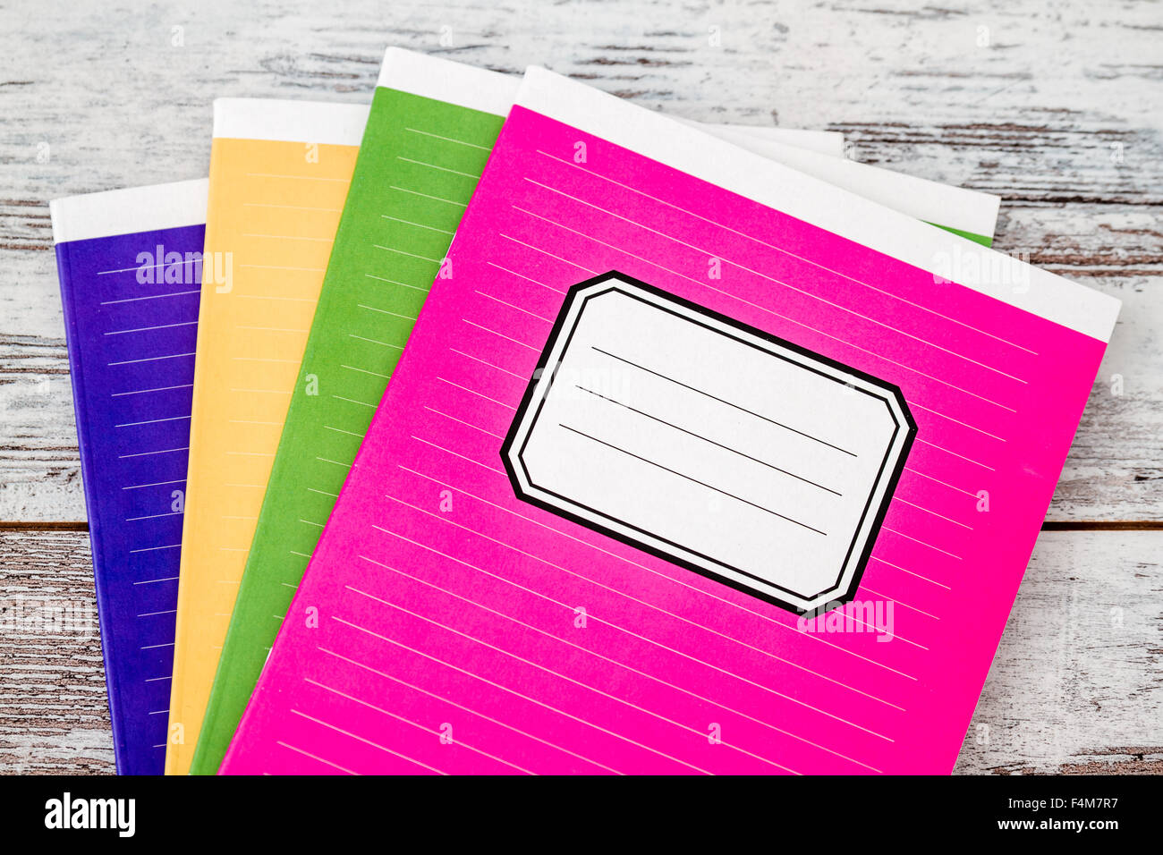 colorful notebooks with name label on cover on white wooden stock