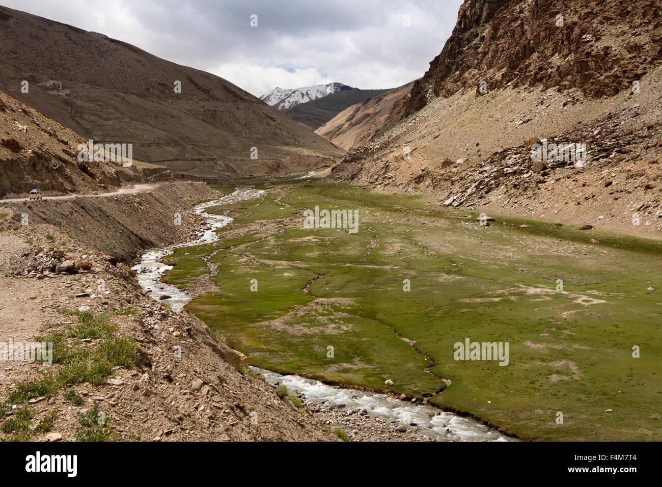 India, Jammu & Kashmir, Ladakh, Rumtse, high altitude road to Taglang La pass above meltwater stream - Stock Image