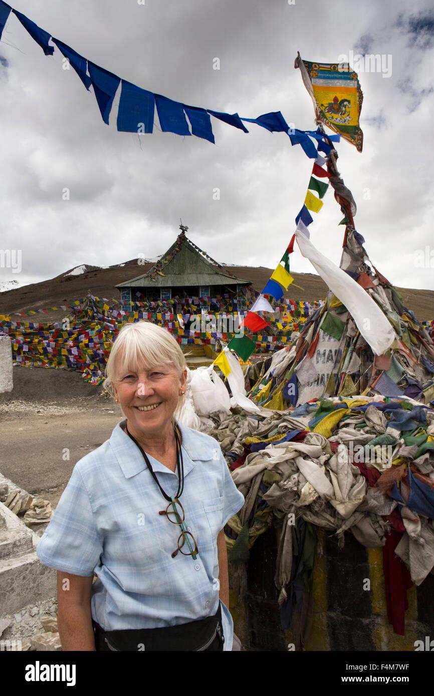 India, Jammu & Kashmir, Ladakh, Taglang La pass top, female tourist at 17,582,foot (5328m) summit prayer flags - Stock Image