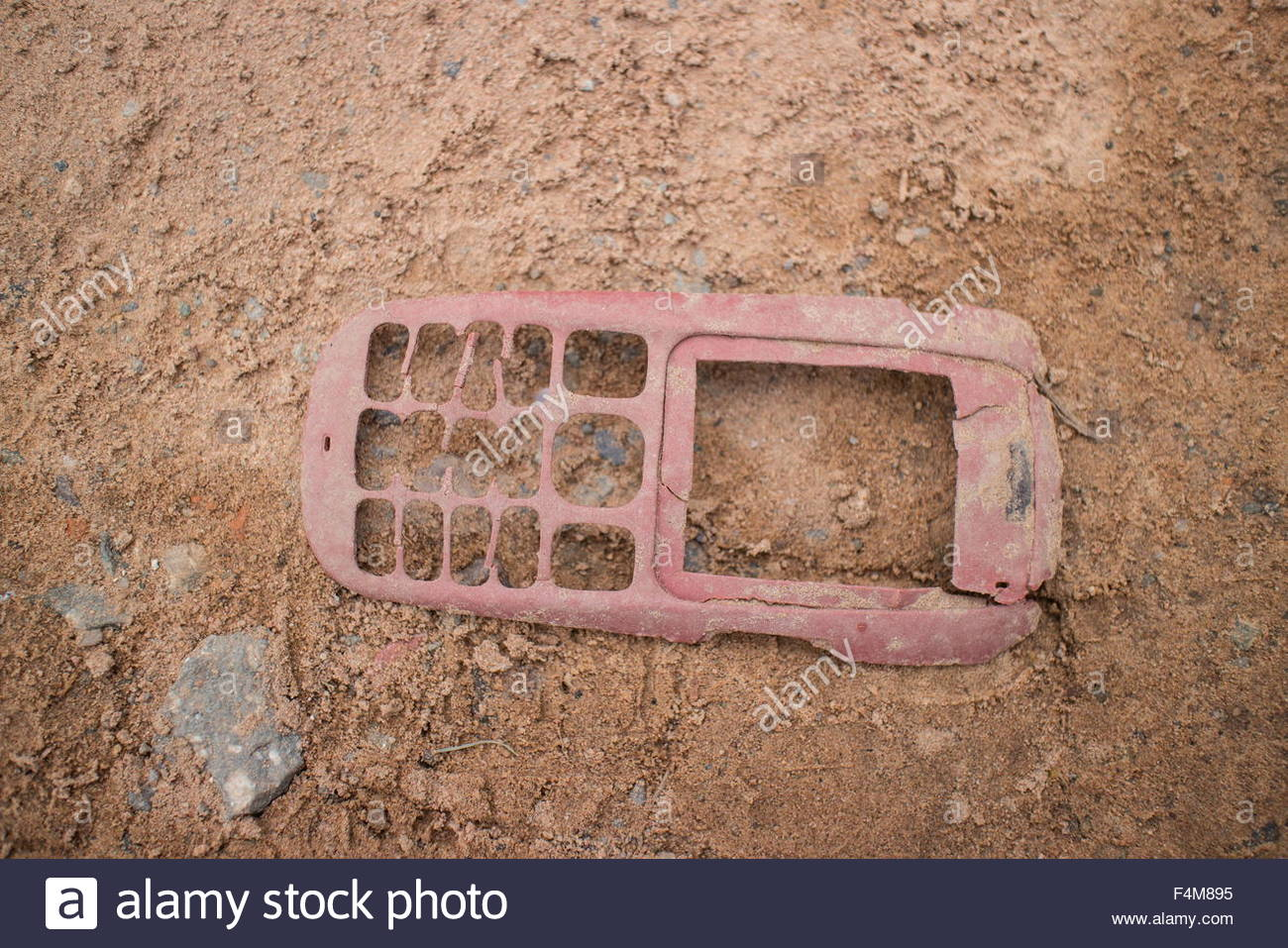 Medium horizontal shot of a dusty, broken older style mobile phone face lying in the dust at the side of the road. - Stock Image