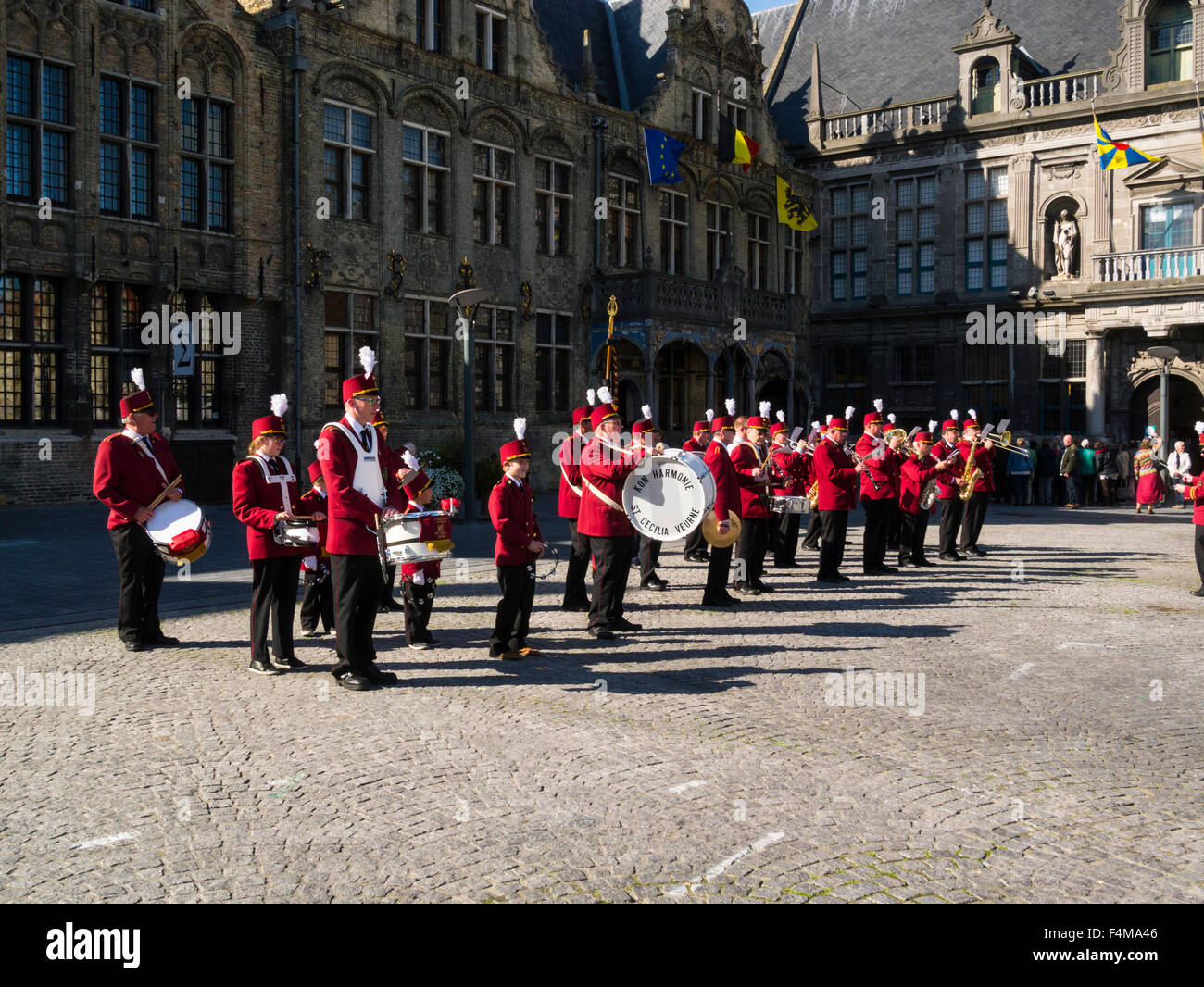 St Cecilia Kon Harmonie Band in red uniforms entertaining visitors Grote Markt market square Veurne West Flanders - Stock Image