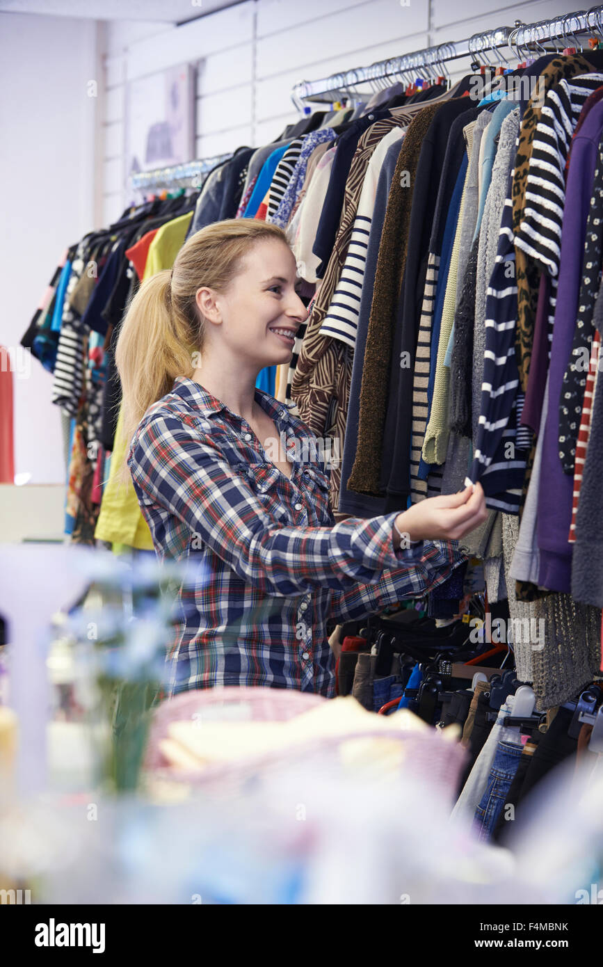 Female Shopper In Thrift Store Looking At Clothes - Stock Image