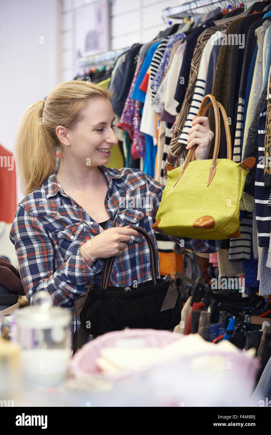 Female Shopper In Thrift Store Looking At Handbags - Stock Image
