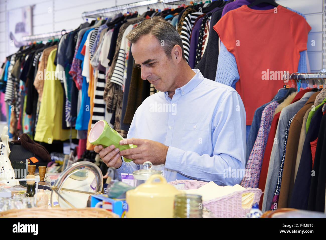 Male Shopper In Thrift Store Looking At Ornaments - Stock Image