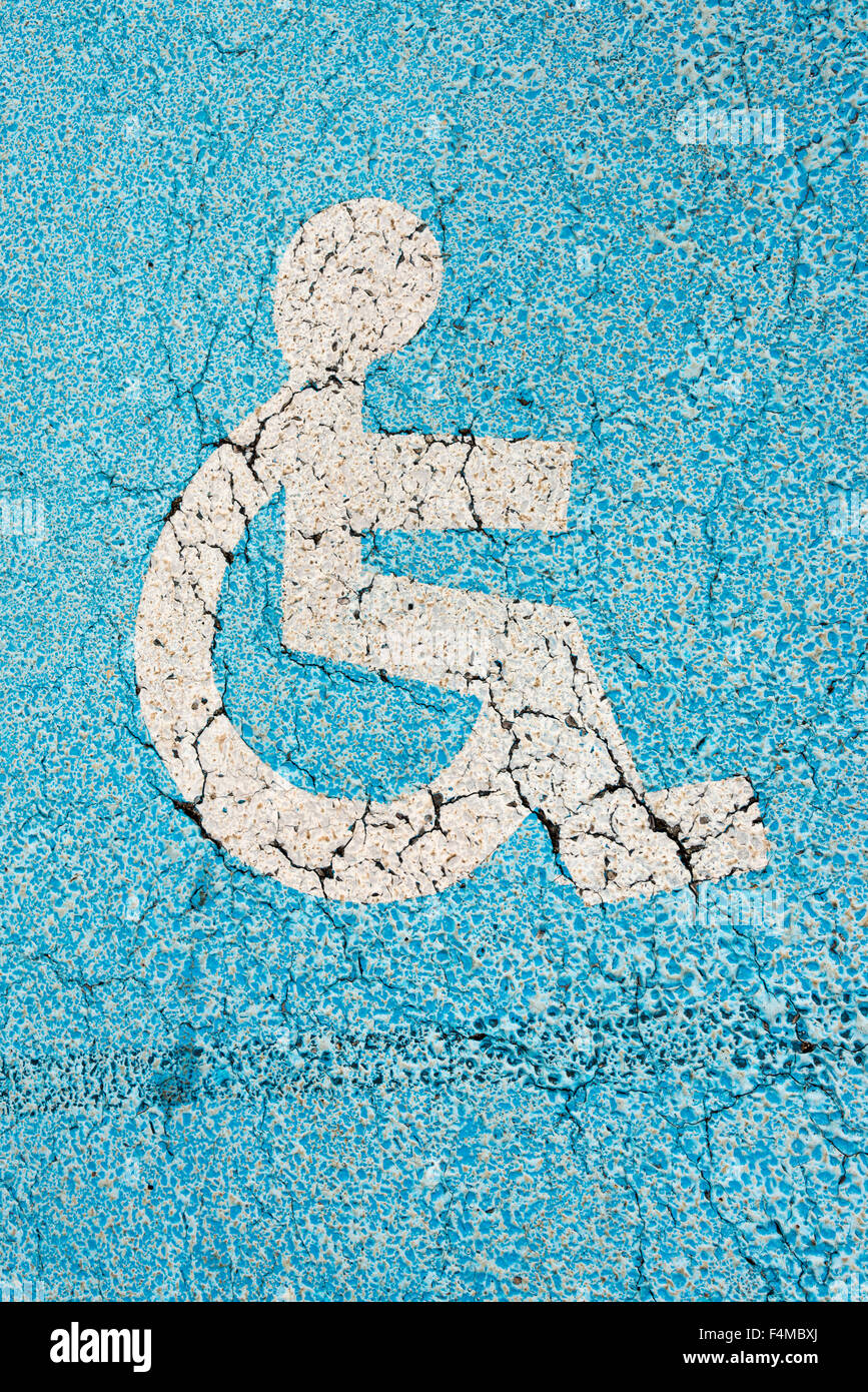 A photo of a blue disabled parking sign painted on the ground in a car park - Stock Image
