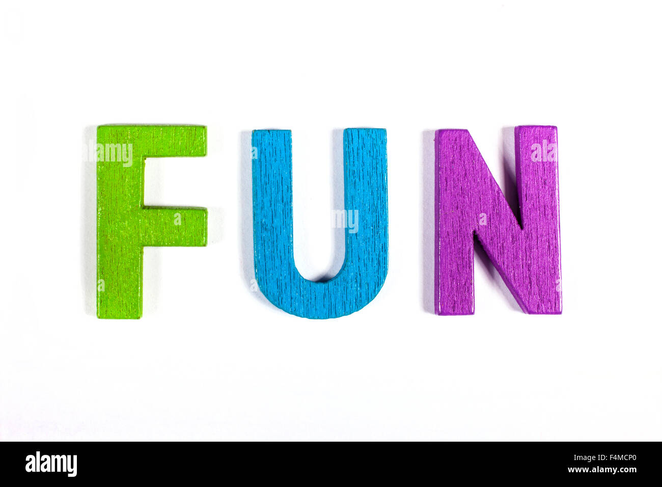 FUN spelt out with bright coloured letters over a white background. - Stock Image