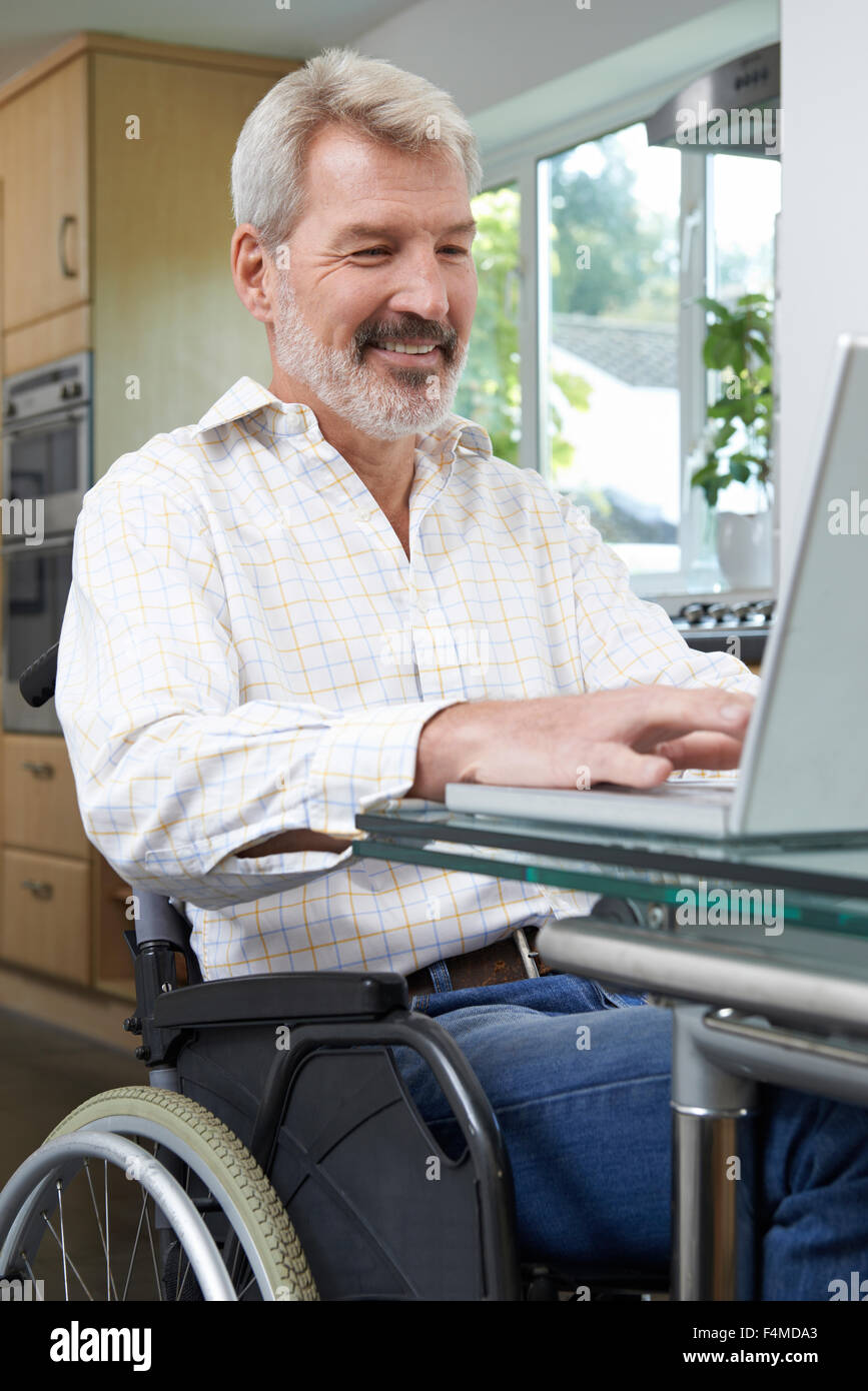 Disabled Man In Wheelchair Using Laptop At Home - Stock Image