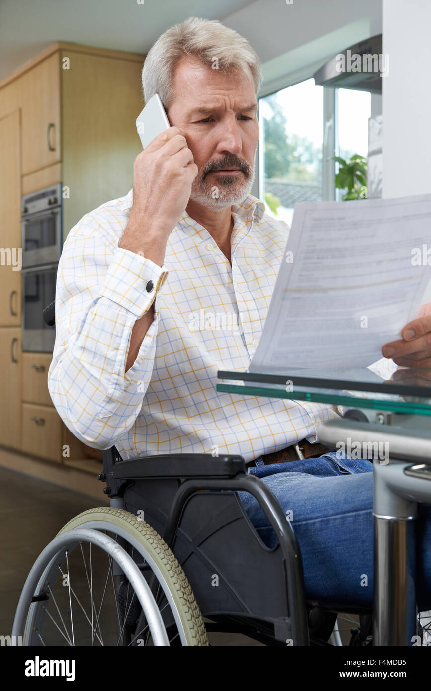 Frustrated Man In Wheelchair Making Phone Call Whilst Reading Letter - Stock Image
