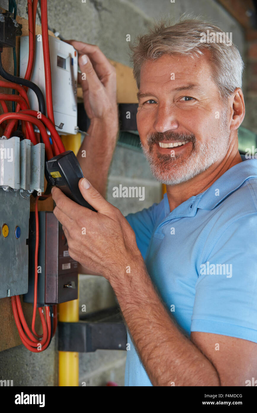 Portrait Of Man Taking Electricity Meter Reading - Stock Image