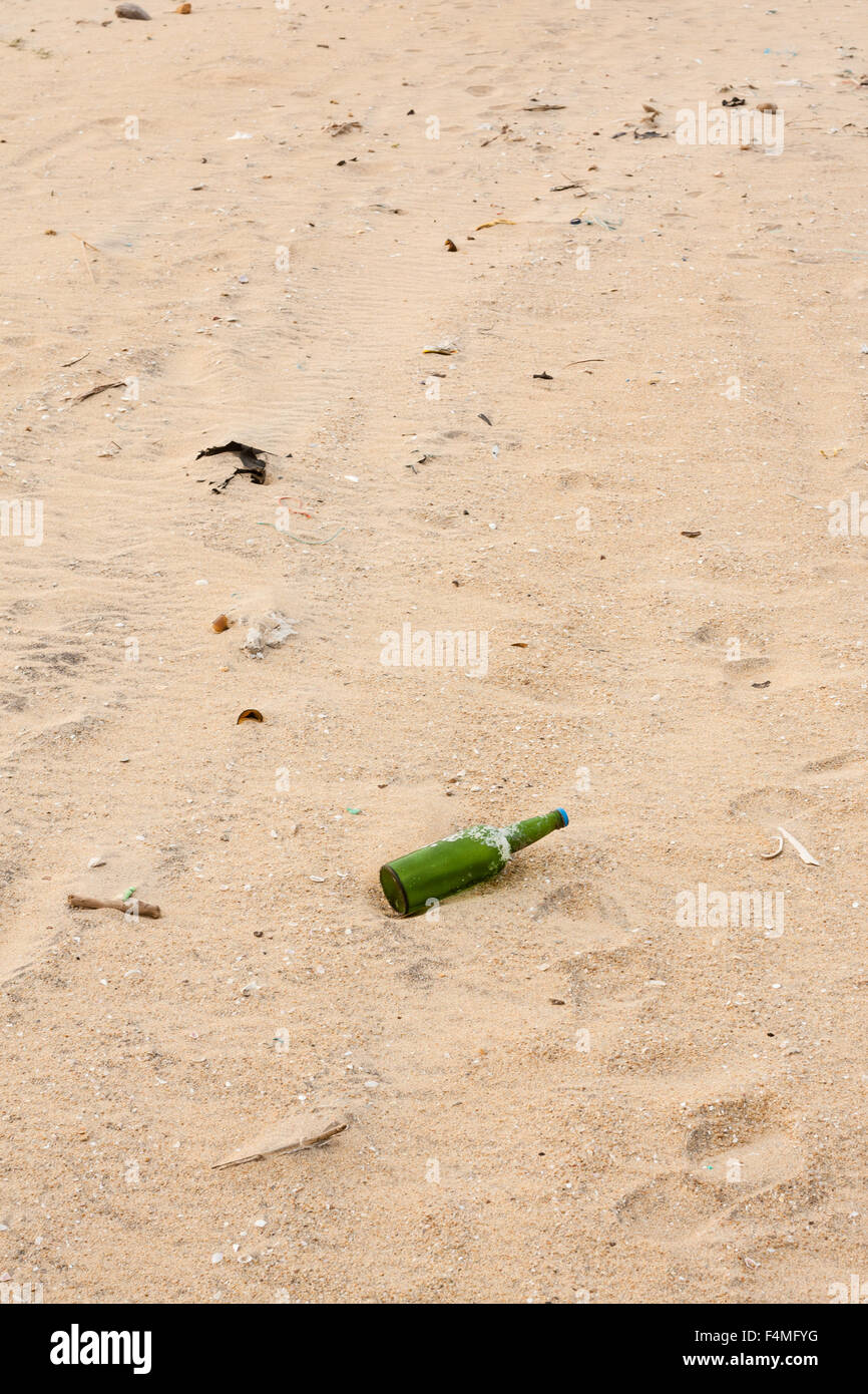 Broken bottles and other garbage lying scattered on a beach. - Stock Image