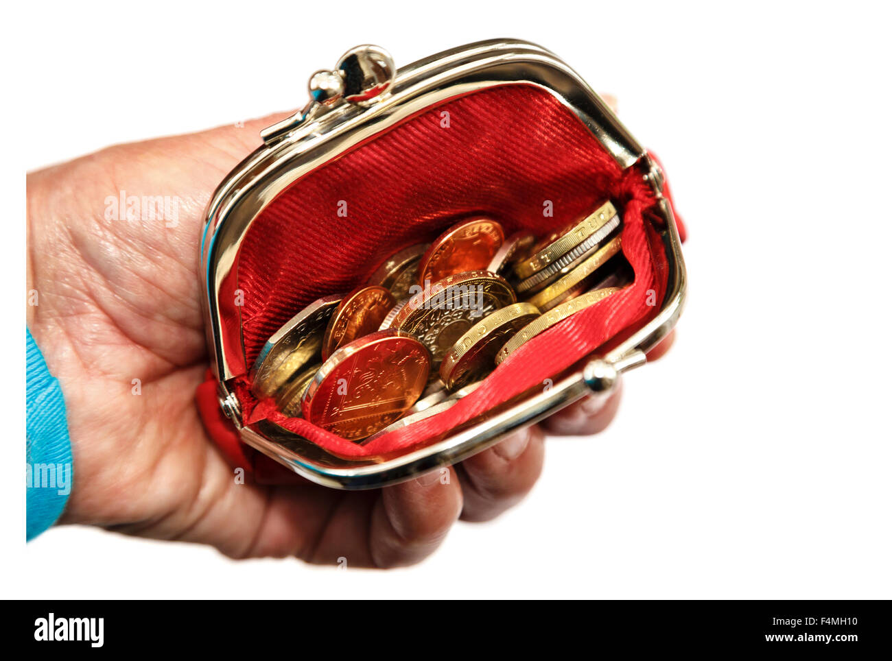 Pensioner's hand holding a red open coin purse with money sterling coins GBP isolated on a white background - Stock Image