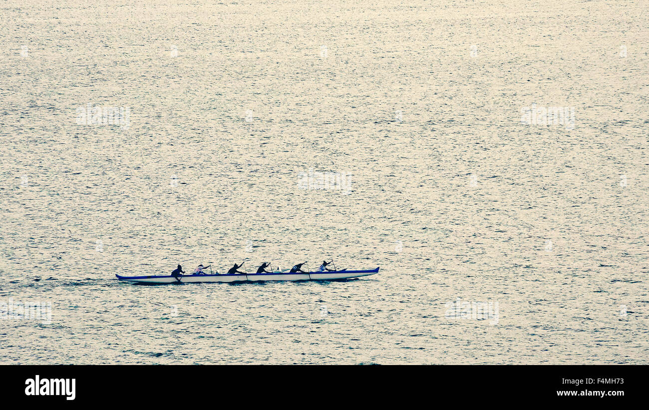 An outrigger canoe team practices rowing in the protected harbor waters of Lahaina, Maui - Stock Image
