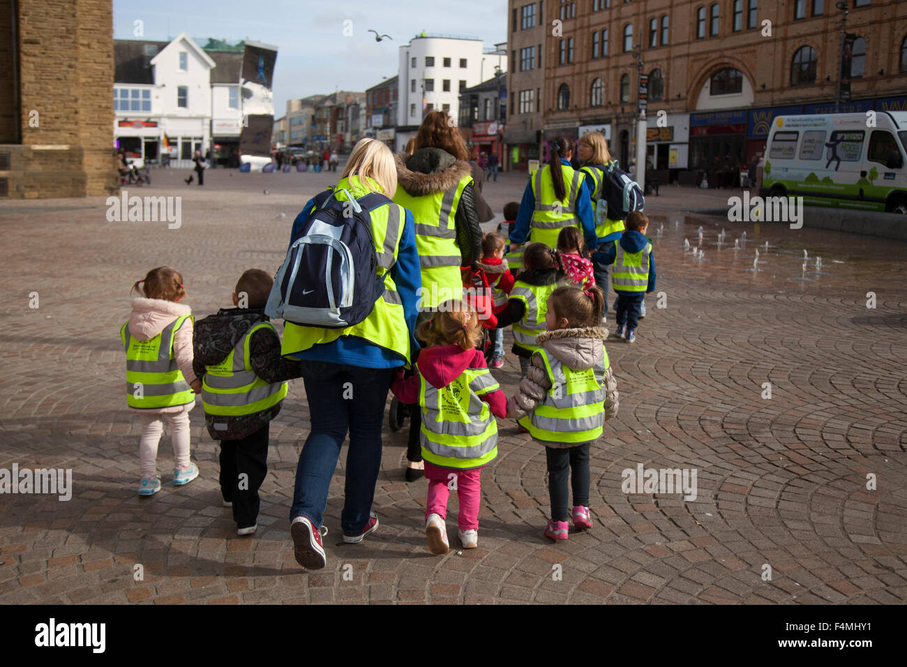 Safeguarding Pre-School primary children wearing protective fluorescent hi-vis hazard jackets on walk around Blackpool - Stock Image