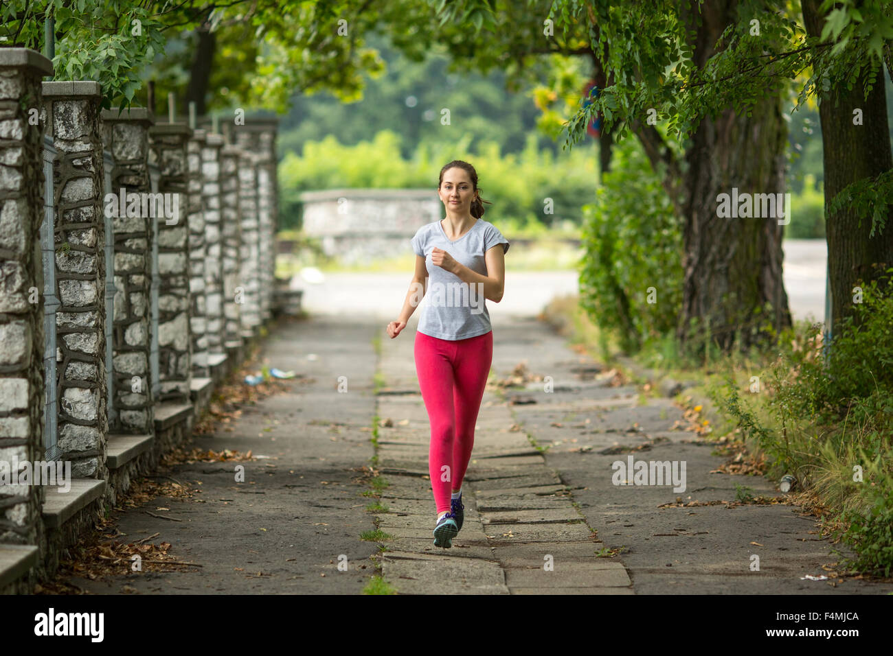 Young girl during a morning jog in the Park. - Stock Image
