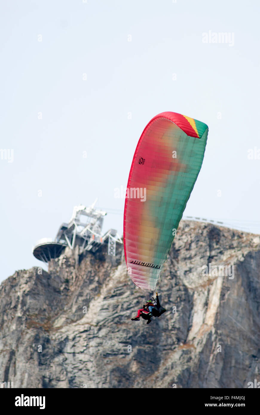 Para glider pilot flying tandem with passenger, gliding in below Le Brevent Cable car - Stock Image