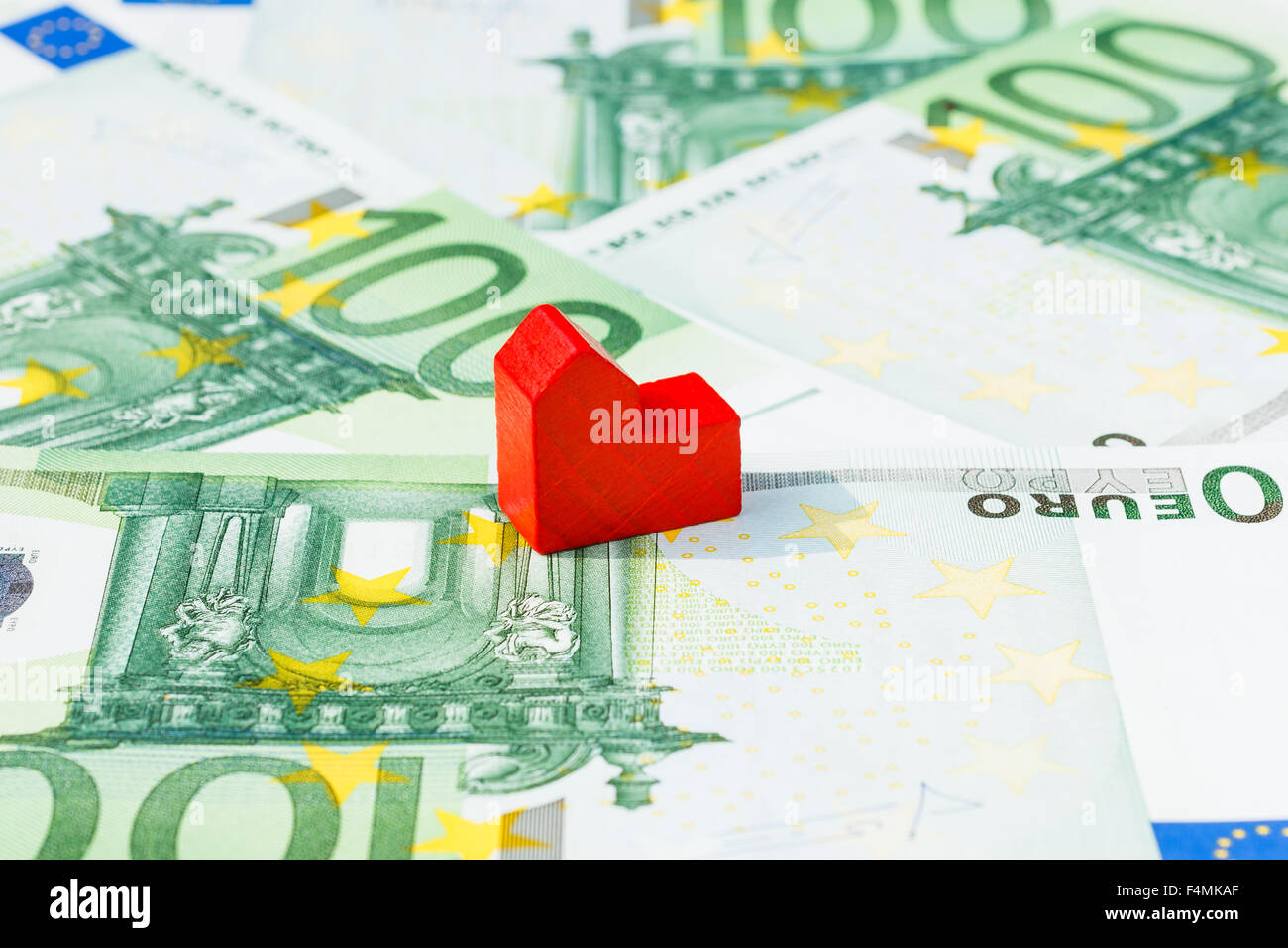 Concept house sell, foreclosure, debt, bill, mortgage on hundred euro banknotes. Focus on red house. - Stock Image