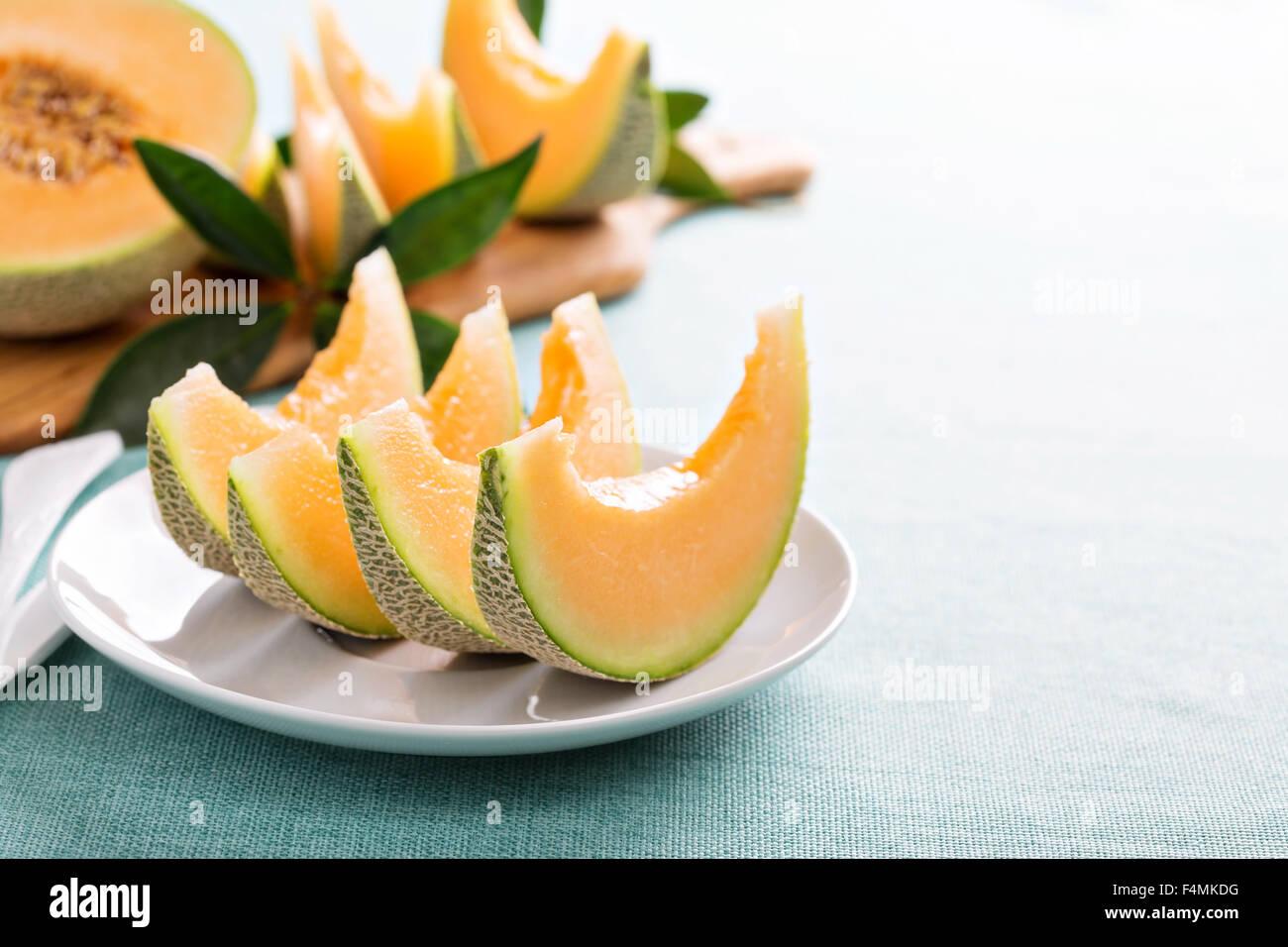 Ripe fresh cantaloupe slices on white plate - Stock Image