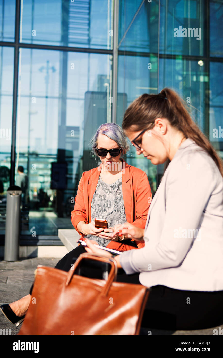 Businesswomen using technologies while sitting at railroad station - Stock Image