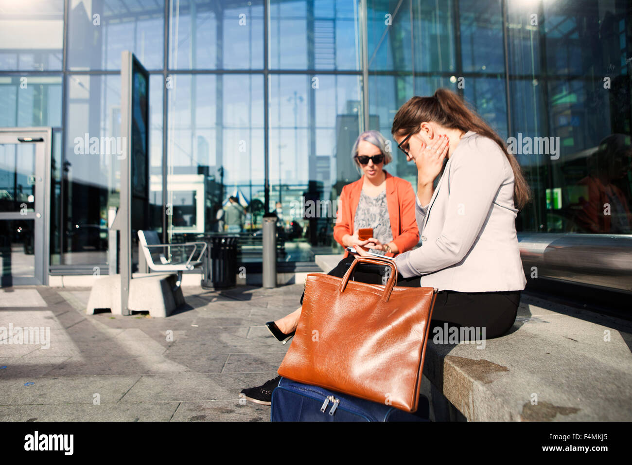 Businesswomen using technologies while waiting at railroad station - Stock Image