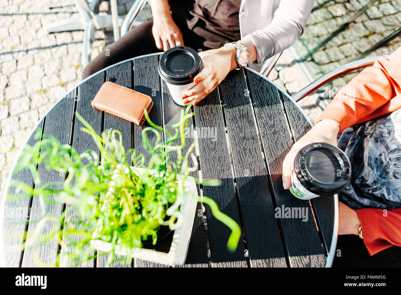 Cropped image of businesswomen holding disposable cups at sidewalk cafe table - Stock Image