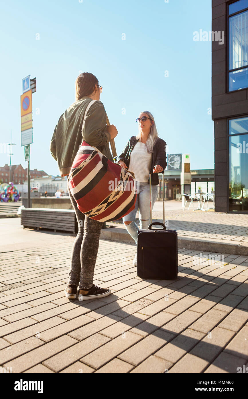 Female university students with luggage standing in city - Stock Image