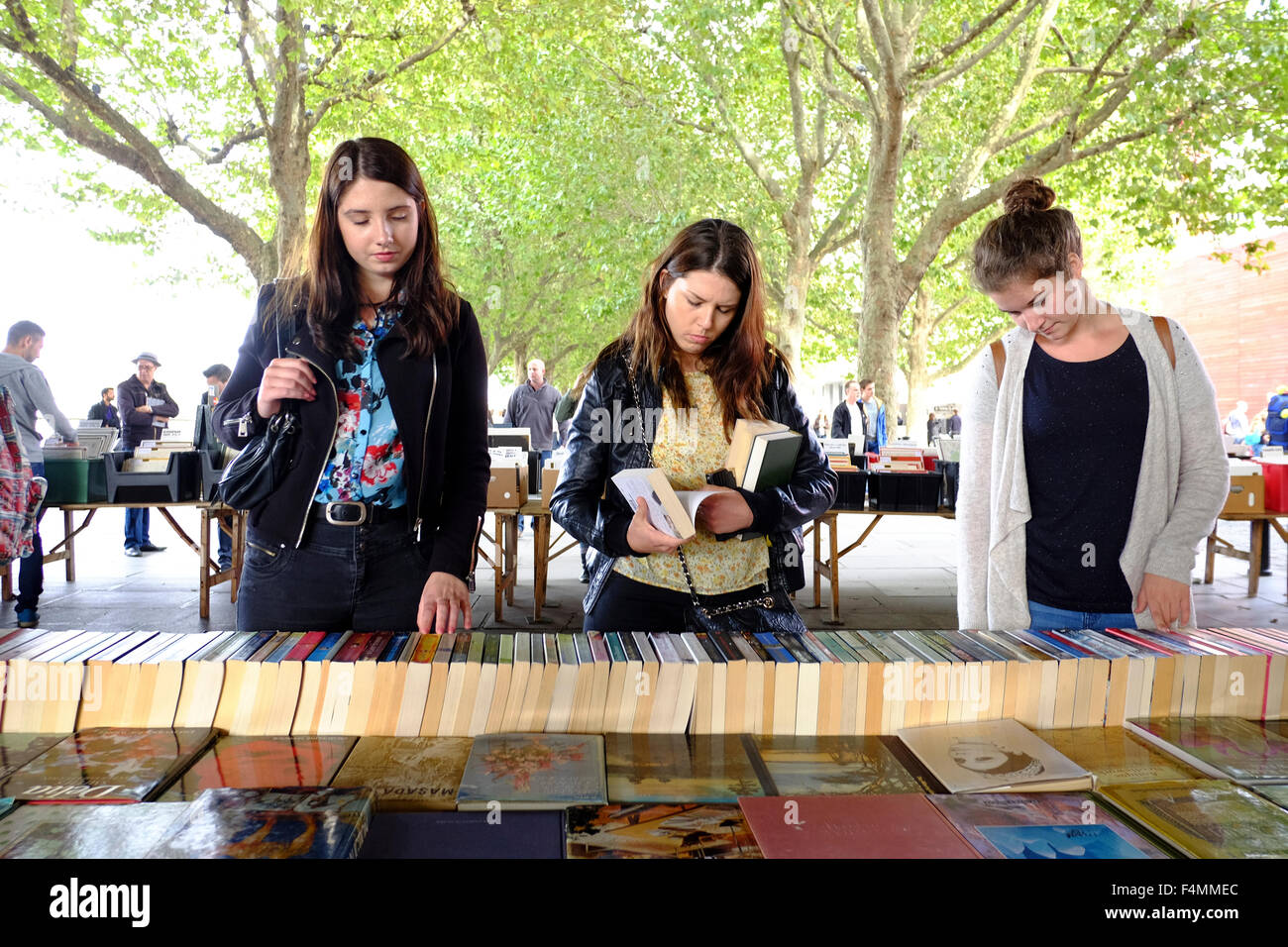 Three Girls Browsing at Southbank Centre's Book Market - Stock Image