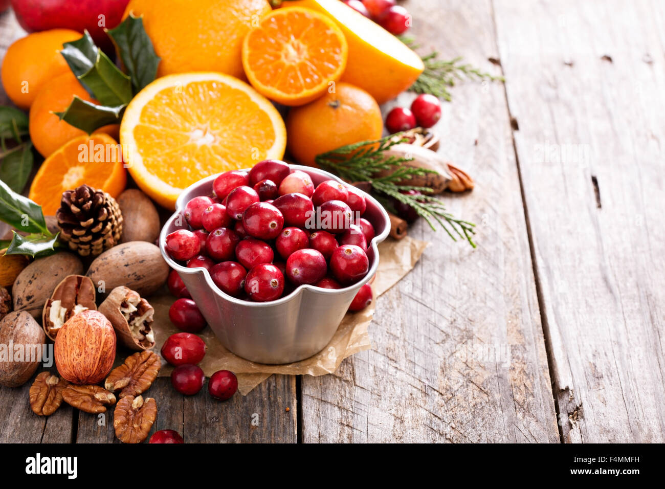 Fall and winter ingredients still life with oranges, cranberry, nuts and spices - Stock Image