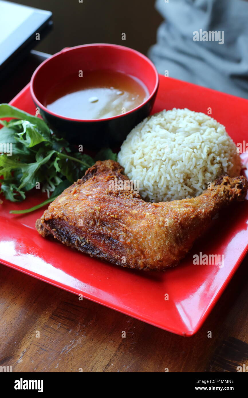 Chicken Rice with Deep Fried  Chicken and broth on a  red Plate - Stock Image