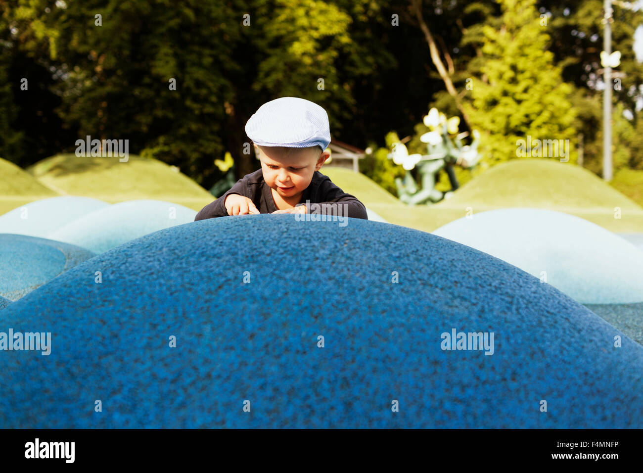 Cute boy leaning on artificial hill in park - Stock Image