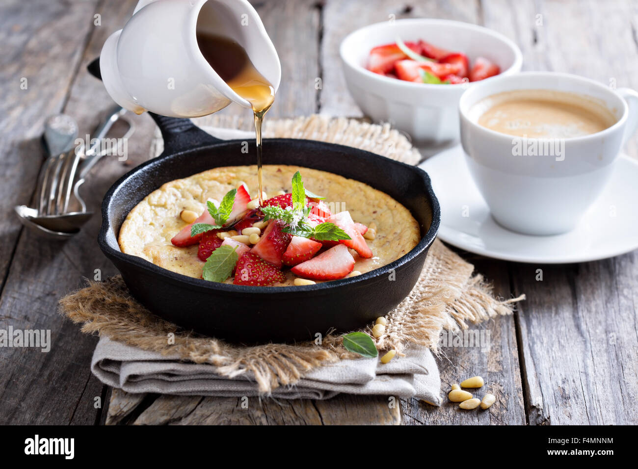 Baked pancake in cast iron pan with fresh strawberries and pine nuts - Stock Image
