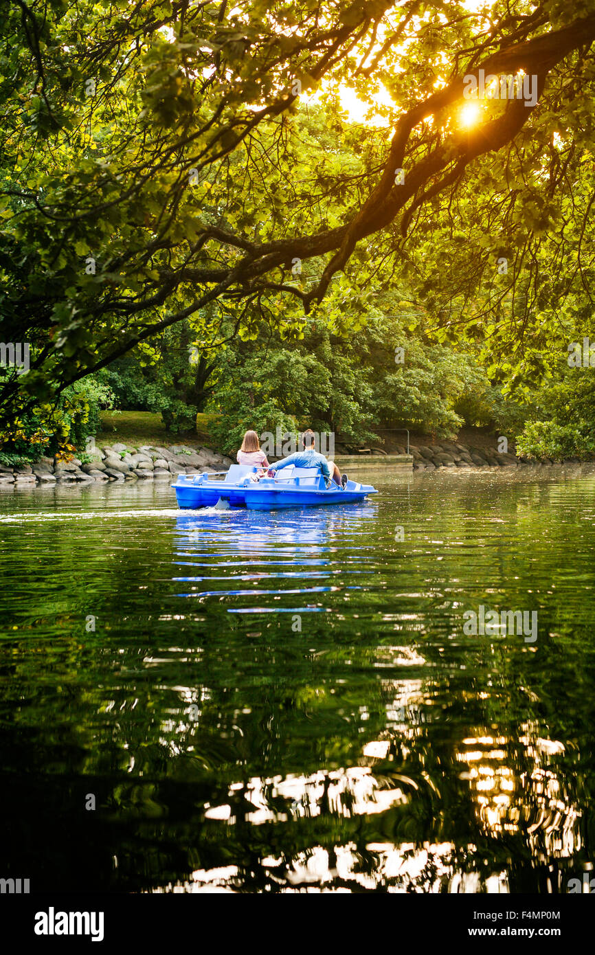 Rear view of friends pedal boating on channel against trees - Stock Image